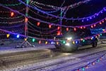 Civilian truck in background, five strings of colorful lights in forground