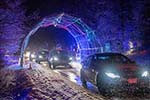 Civilian cars lined up underneath metal arch with Christmas lights