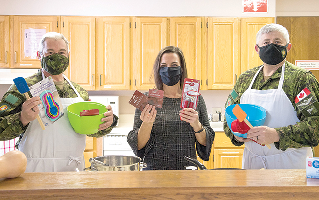 Three people holding cooking supplies in kitchen