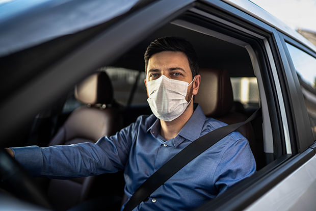 Man in drives seat of car, wearing face mask